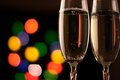 Two glasses of champagne toasting against bokeh lights background Stock Photos