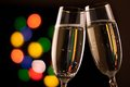 Two glasses of champagne toasting against bokeh lights background Stock Images