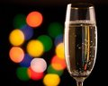Two glasses of champagne toasting against bokeh lights background Royalty Free Stock Images