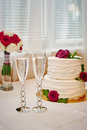 Two glasses of champagne and wedding cake on the table Royalty Free Stock Photo