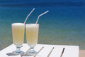 Two glasses of cocktail of Pina Colada against the sea. Royalty Free Stock Photo