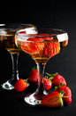 Two glasses of cold champagne with strawberries on a black background close up Stock Photo