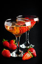 Two glasses of cold champagne with strawberries on a black background close up Stock Images