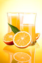 Two Glasses of Fresh Orange juice, half oranges Royalty Free Stock Photos