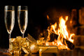 Two glasses in front of fireplace and gift boxes Stock Photos
