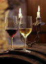 Two glasses full of wine romantic atmosphere with one red and the other white Stock Image