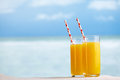 Two glasses of orange juice cocktail on white sandy beach Royalty Free Stock Photo