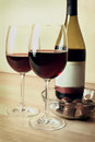 Two glasses of red wine and chocolates on table Royalty Free Stock Photography