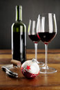 Two glasses of red wine and christmas baubel bottle very shallow dof on star the Stock Photography