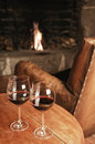 Two glasses of red wine at a cosy fireplace and some cheese selective focus Stock Image