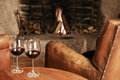 Two glasses of red wine at a cosy fireplace and some cheese selective focus Stock Photos