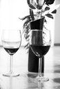 Two glasses of red wine and rose in a vase black white Royalty Free Stock Image
