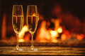 Two glasses of sparkling champagne in front of warm fireplace. C Royalty Free Stock Photo