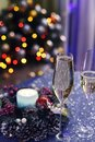 Two glasses of sparkling wine champagne, a Christmas wreath and the lights of the New Year tree in the background. Royalty Free Stock Photo