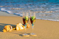 Two glasses in a wave of the sea on the beach Royalty Free Stock Photo