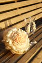 Two glasses and a wedding bouquet on wooden bench at sunset Royalty Free Stock Photos