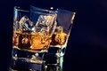 Two glasses of whiskey with ice cubes on black background with light tint blue and reflection time relax whisky Stock Photo