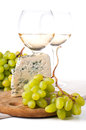 Two glasses of white wine, cheese and a grapes Stock Image