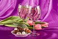Two glasses of white wine, flowers and sweets Royalty Free Stock Photo
