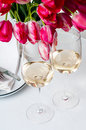 Two glasses of white wine on a table with bouquet bright pink tulips in vase and cutlery Royalty Free Stock Images