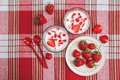 Two Glasses of Yogurt,Red Fresh Strawberries are in the Ceramic Plate with Plastic Spoons on the Check Tablecloth.Breakfast Organi