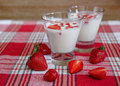 Two Glasses of Yogurt,Red Fresh Strawberries on the Check Tablecloth.Breakfast Organic Healthy Tasty Food.Cooking Vitamins Ingredi Royalty Free Stock Photo