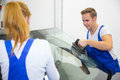 Two glaziers or mechanics replace windshield or windscreen on car replacement a by couple of in garage Stock Image