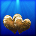 Two golden hearts as a symbol of love Royalty Free Stock Photos