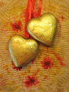 Two golden hearts on colorful background Royalty Free Stock Images