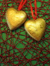 Two golden hearts on colorful background Stock Photography