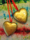 Two golden hearts on colorful background Royalty Free Stock Image
