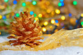 Two golden pine cone on snowy winter and lights background Stock Images