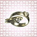 Two golden rings with hearts and diamonds Stock Photos