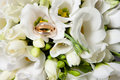 Two golden wedding rings beautiful bouquet white freesias Royalty Free Stock Images