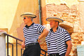 Two gondolier on the docks awaiting tourists in Venice, Italy Royalty Free Stock Photo