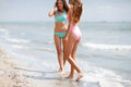 Two good-looking young girls in colorful swimsuits on a sea background. Ladies walking along a beach. Copy space. Royalty Free Stock Photo