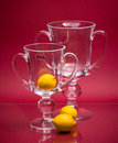 Two graceful cups and three yellow fruits on pink Stock Photo
