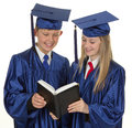 Two graduate children reading a book Royalty Free Stock Photography