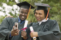 Two graduates looking at cellphone happy multiethnic male cell phone outside Royalty Free Stock Photography