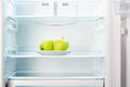Two green apples on white plate in open empty refrigerator Royalty Free Stock Photo