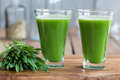 Two green barley grass shots on a wooden background Royalty Free Stock Photo