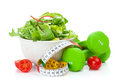 Two green dumbells, tape measure and healthy food. Fitness and h Royalty Free Stock Photo