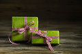 Two green gifts with red white checkered ribbon on wooden backgr Royalty Free Stock Photo