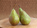 Two green pears on a wooden plate Stock Photos