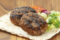Two grilled burgers with salad and a pita on a wooden plate Royalty Free Stock Photography