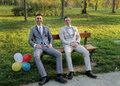 Two groom sit on the bench and laughing Royalty Free Stock Images