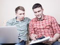 Two guys with gadgets young attractive using laptop computer on sofa at home Stock Images
