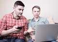Two guys with gadgets young using on sofa at home Stock Photo