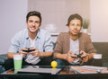 Two guys playing on the console sitting on the couch Royalty Free Stock Photo