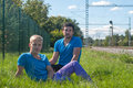 Two guys sitting in a grass an blue t shirts Royalty Free Stock Photos